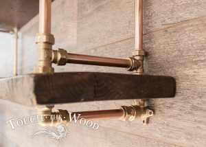 closeup of copper pipe bookshelf with brass - steampunk industrial style